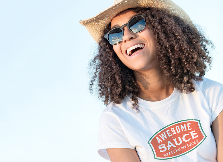Girl in a Straw Hat and Sunglasses, smiling wearing a classic t-shirt with an Awesome Sauce design