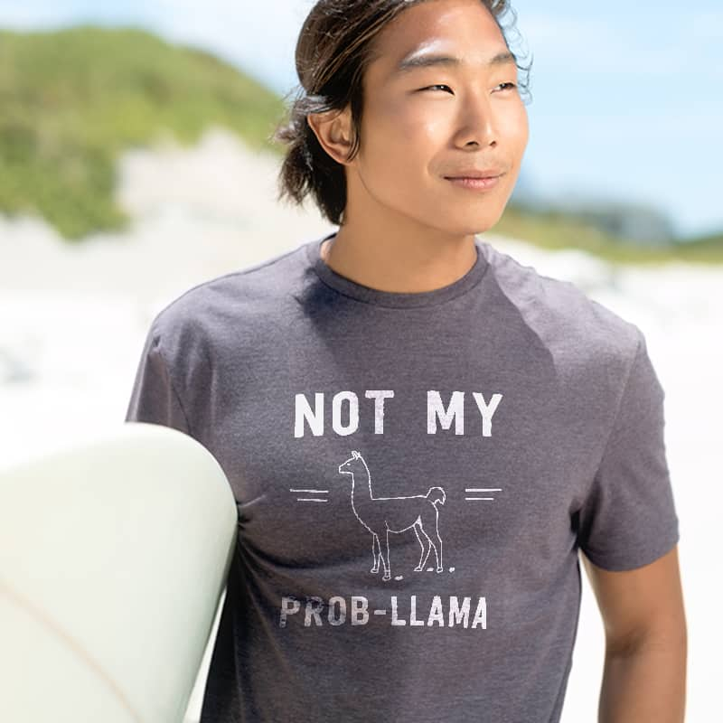 Surfer wearing funny custom printed t-shirt with llama illustration and text which reads: Not my prob-llama.