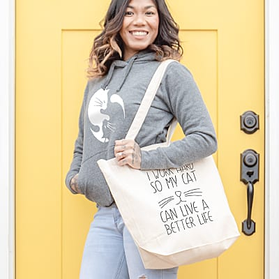 Woman wearing hoodie and holding tote bag with custom printed cat designs.