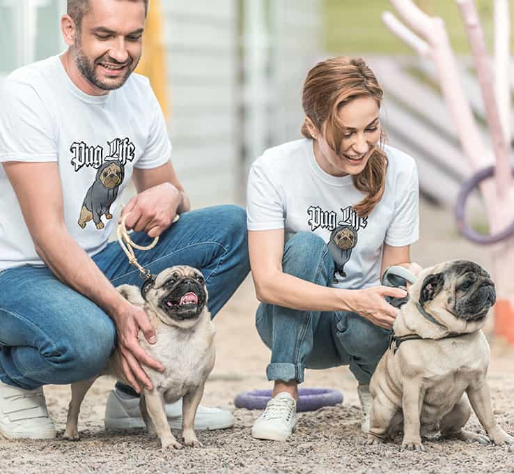 Two rescue pugs being walked by man and woman in custom design t-shirts with pug illustration and text that reads Pug Life in a gothic font.