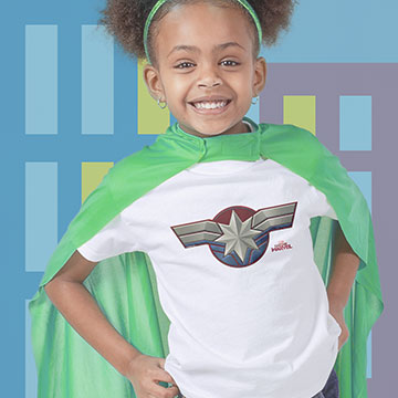 Little girl dressed as a super hero wearing t-shirt with official Captian Marvel design printed on the front.