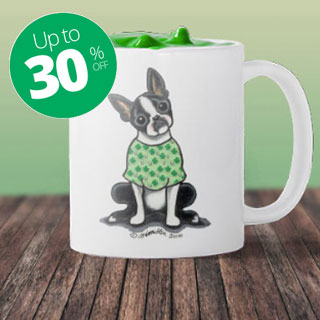 White mug on wood surface with dog in St. Patrick's Day shirt.