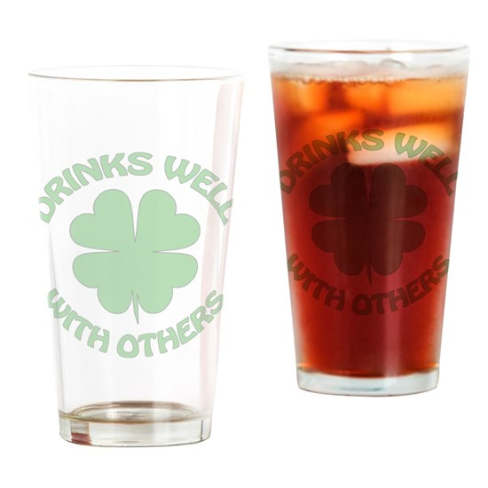 Drinking glass with funny St. Patrick's Day design that reads Drinks Well With Others