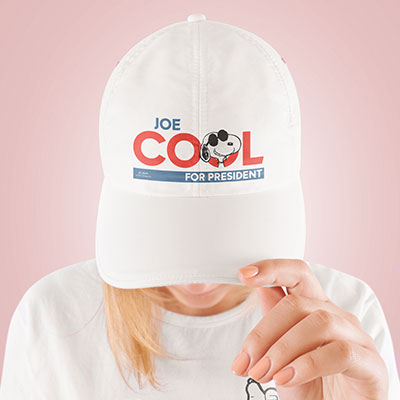 Woman wearing a white cap with a official licensed Peanuts Joe Cool for President design custom printed on the front.