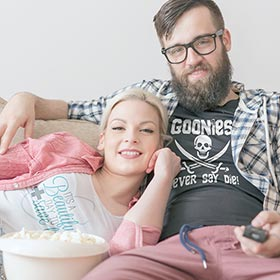 Man and Woman sitting in Cafepress personalized T-shirts watching TV