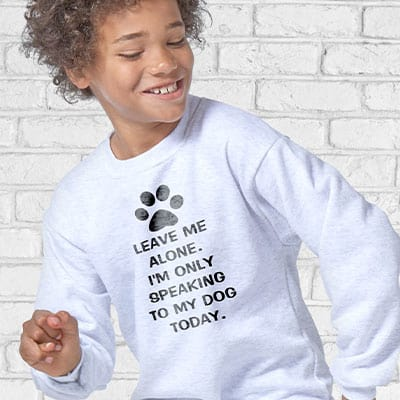Young boy wearing a sweatshirt with a custom pets design showing a paw print and text which reads: Leave me alone, I'm only speaking to my dog today.