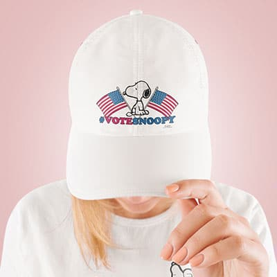 Woman wearing a white cap with a official licensed Peanuts Vote Snoopy election 2020 design custom printed on the front.