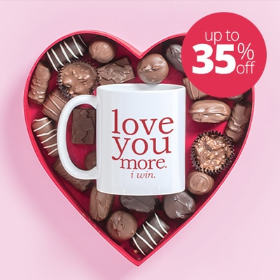 Mug in the middle of box of chocolates with I Love You More design.