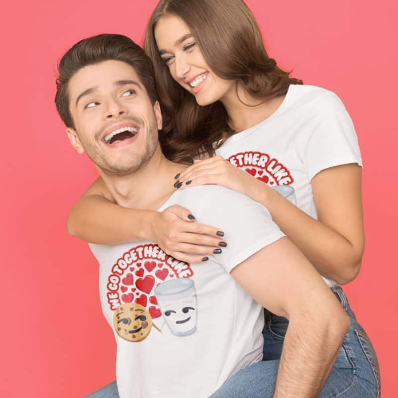 Young couple in custom printed white t-shirts with funny emoji milk and cookies design and text which reads: We go together like...