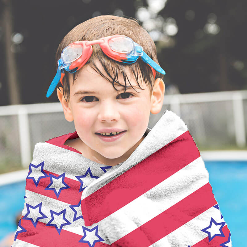 Image of young boy who just got out of the pool and is covering himself with a beach towel. The beach towel has a custom designed American flag graphic printed on it.