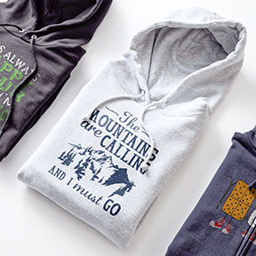 Image of a folded gray heather hoodie with a funny camping custom design on the front showing mountains and text that reads: The Mountains Are Calling and I Must Go.