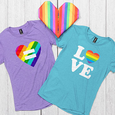 Image of two t-shirts connected by a hand crafted rainbow flag heart. The shirts have Gay Pride designs on the front that read: Love - with a rainbow heart graphic, and a rainbow heart with an equal sign in the middle.