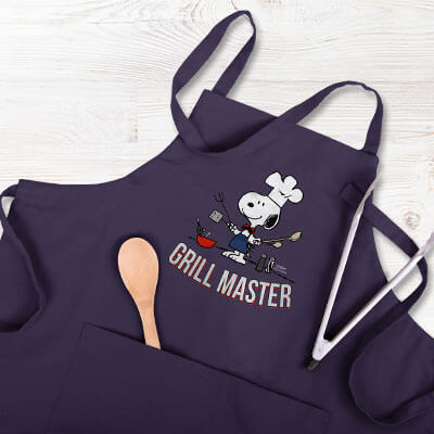 Image of a blue apron lying on an outdoor wood deck surrounded by grilling tools. The apron has a custom licensed Peanuts design with Snoopy in a chef's hat and apron holding gilling implements with text that reads: Grill Master.