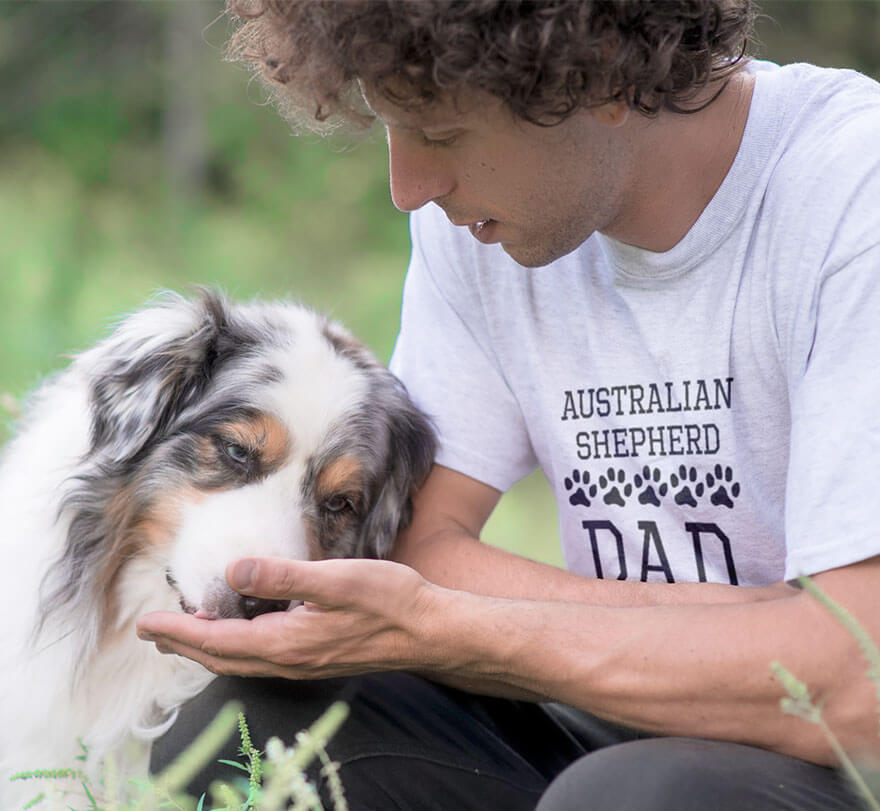 Man in a field with his Australian Shepherd dog. He is wearing a graphic t-shirt with the breed of dog on the front.