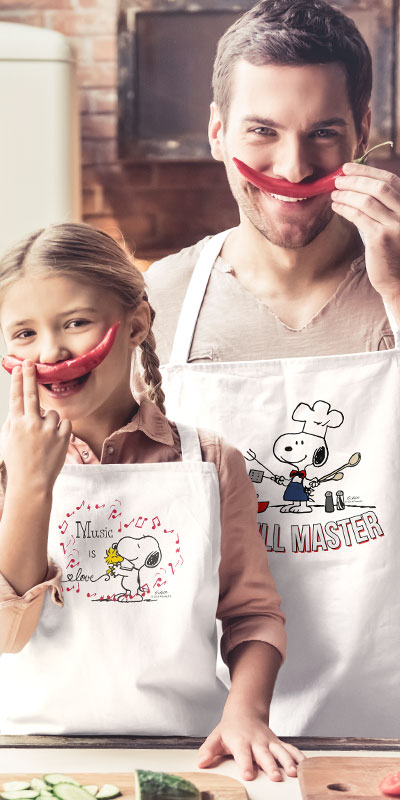 Father and daughter cooking in the kitchen and holding up peppers as moustaches. Both are wearing custom printed aprons. The Dad's apron has Snoopy Peanuts Grill Master design and the daughter's apron has a Peanuts Snoopy and Woodstock music design.