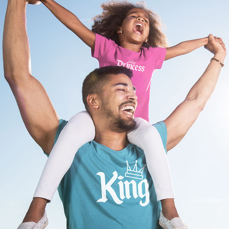 Father with daughter riding on his shoulders. They are both wearing custom printed graphic t-shirts. The father's shirt reads King and the daughters t-shirt reads Princess.