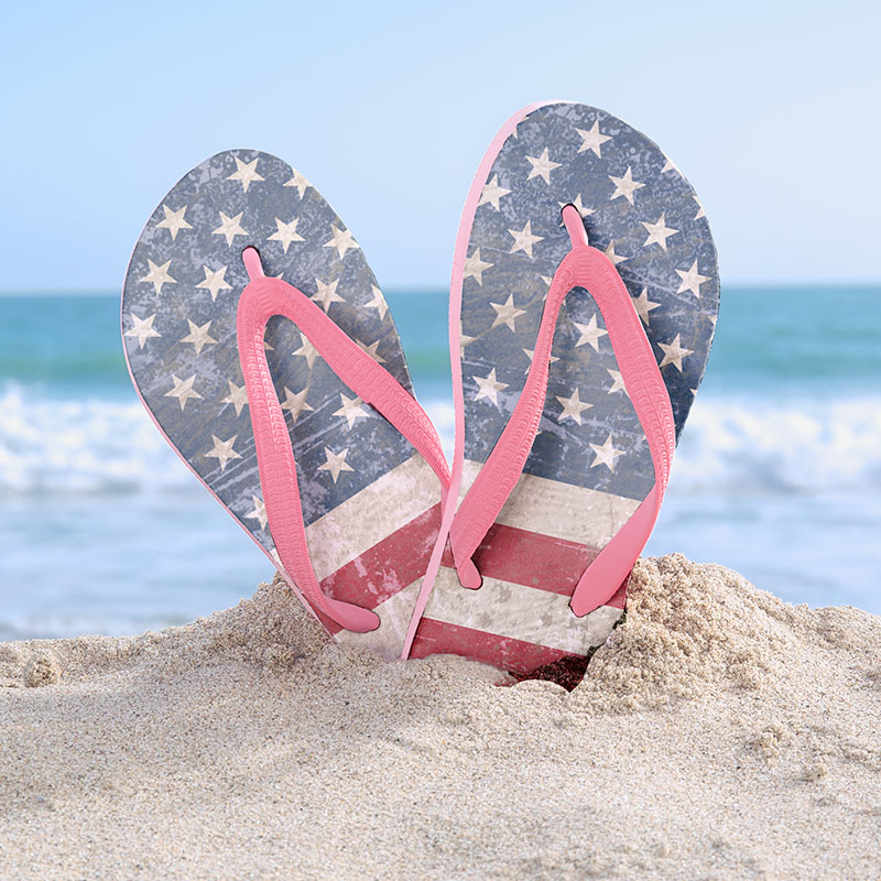 Cool Americana flip flips stuck in the sand with the beach showing behind them. The flips flops have a custom retro American flag image printed on them for Memorial Day. Reg. $19.99 / Save $9.99 / Offer Ends 5/28.