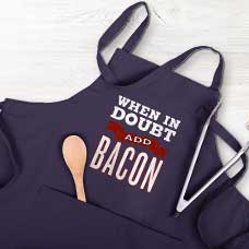 Father and daughter in kitchen laughing at themselves and using peppers to make their smiles. Both are wearing custom printed aprons with funny sayings printed on them. Great idea for a Father's Day gift.