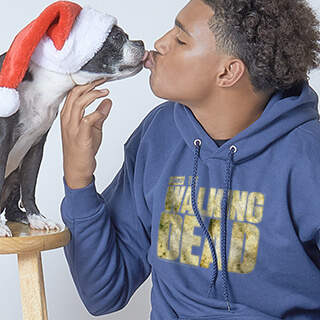 Man wearing a custom designed winter apparel hoodie sweatshirt kissing his pet dog - Boston Terrier. Both are wearing Santa hats.