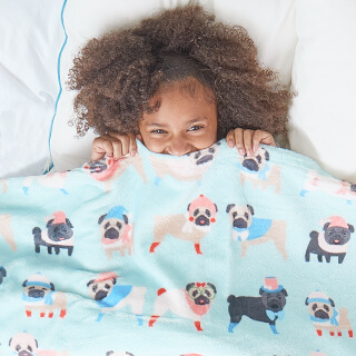 Child covering up part of their face with a custom blanket which has a buffalo plaid print