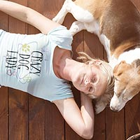 Woman laying on the ground happily in her custom Cafepress T-shirt while her dog lies with her