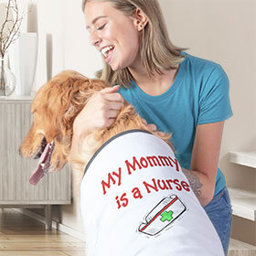 Teenage girl hugging her labrador retriever dog who is wearing a custom printed dog t-shirt that reads: My Mommy is a Nurse.