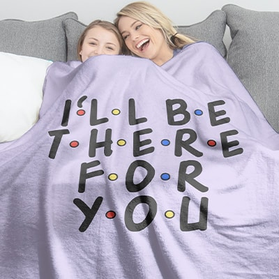 Mom and daughter laying under their officially licensed Friends TV series fleece blanket printed by CafePress