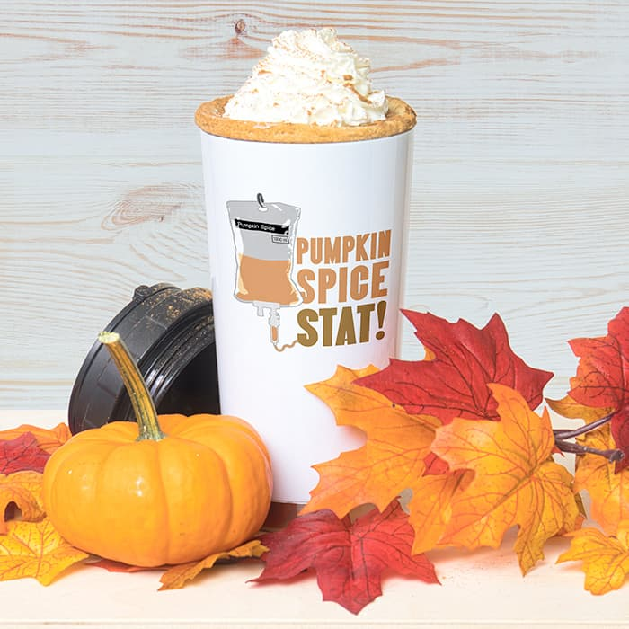 Fall scene with leaves and pumkins and a whipped cream topped drink in a travel mug. The travel mugs has a custom design showing an illustration of an IV bag and text that reads: Pumpkin Spice Stat!