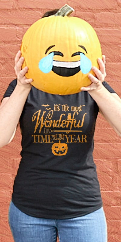 Young person holding a painted pumpkin wearing their custom printed CafePress Halloween design on a dark t-shirt