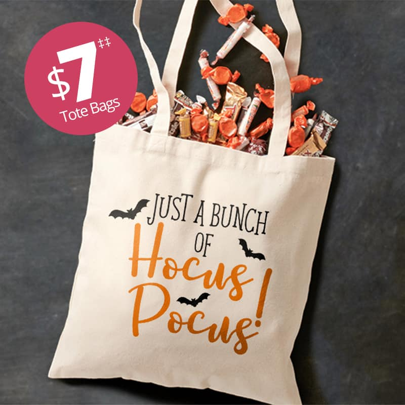 Canvas tote bag filled with Hallowwen candy. Custom printed on the front with bat silhouettes and stylized text that reads: Just a bunch of hocus pocus.