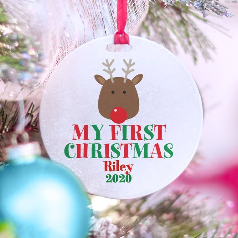 Christmas round holiday ornament with cute reindeer illustration and stylized text that reads: My First Christmas with personalizable name and year.