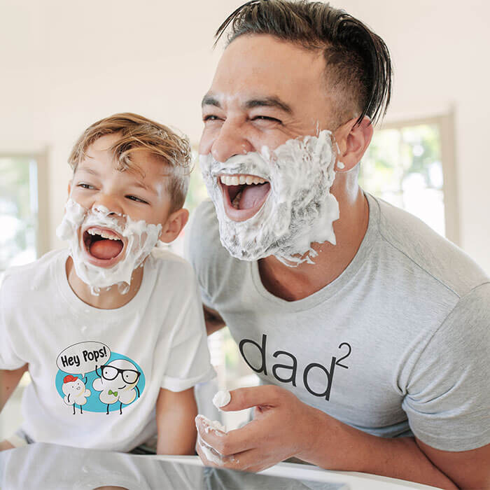 Father and son laughing and pretending to shave together in front of a mirror. Father is wearing a t-shirt with a Dad squared design and son is wearing a t-shirt with a cartoon of popcorn saying Hey Pops.