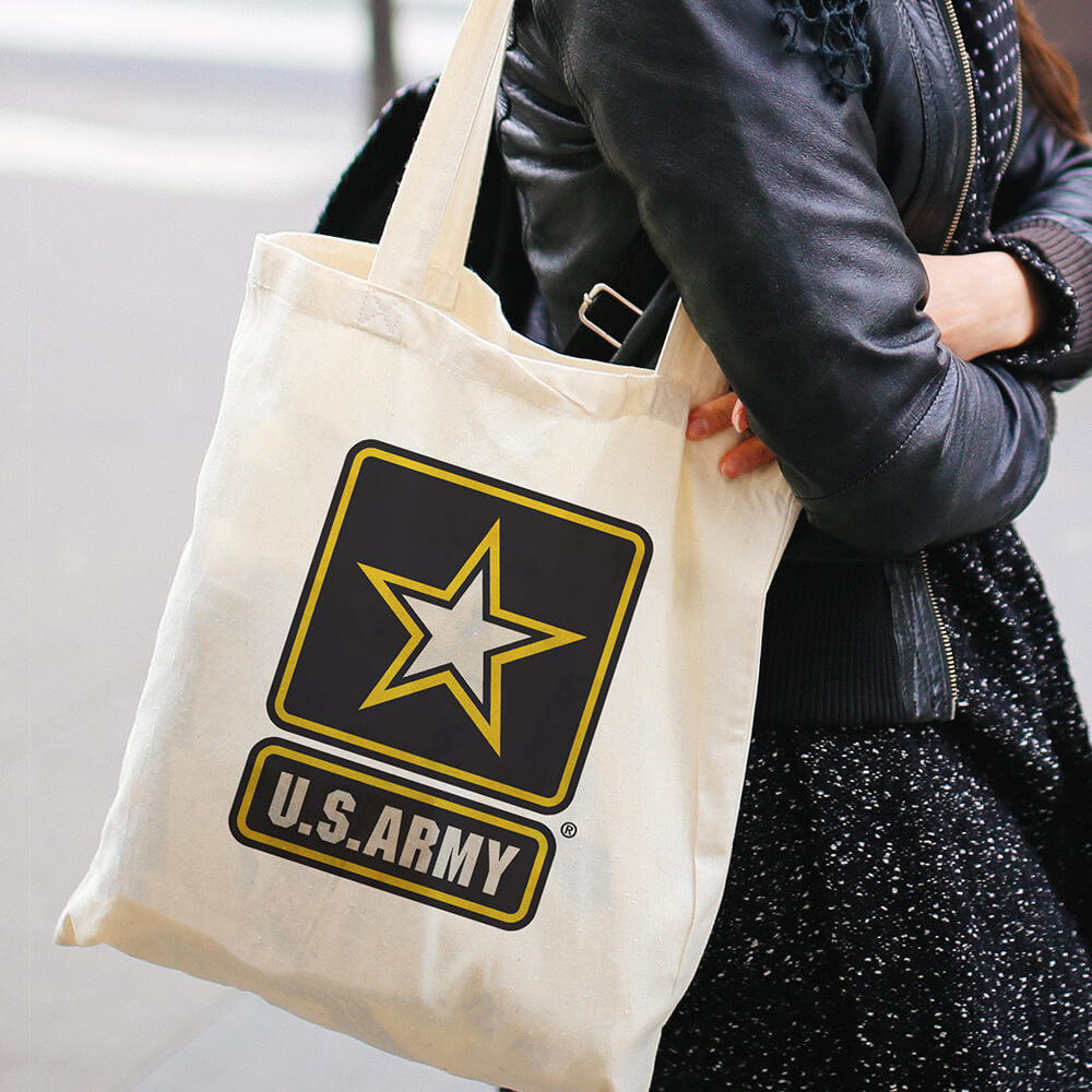 Woman walking down the street carrying a tote bag with official U.S. Army logo printed on the side