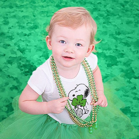 Baby toddler in a field of clovers dressed for St Patrick's Day in a baby onesie, bodysuit, with a funny St Patrick's Day design.
