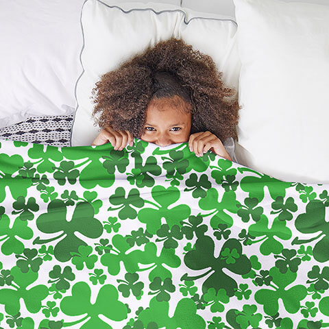 Young girl laying in bed laughing and covering herself with a blanket printed with a St. Patrick's Day clover pattern.