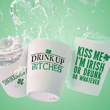 Three shot glasses with hilarious drinking memes printed on them splasing into green beer.