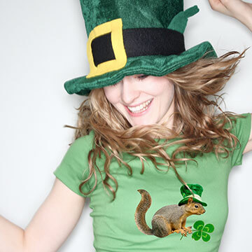Woman wearing a green t-shirt with leprechaun design, as well as, a leprechaun hat. She is dancing and celebrating St Patrick's Day.
