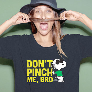 Funny woman in a black t-shirt with an official licensed Peanuts St. Patrick's Day Snoopy design that reads 'Don't Pinch Me Bro'.